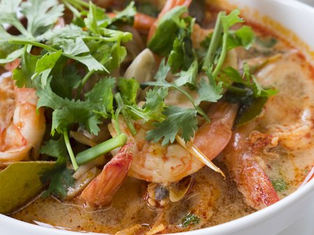 Tom yam kung, the traditional Thai sour soup with prawns and champignons, topped with coriander. The photo shows the red version of the soup, made with coconut milk, also called tom yam kathi. Shallow depth of field.