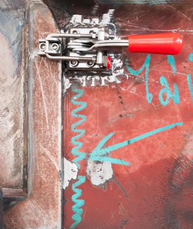 Clamp on door of unfinished machine at a workshop. Stock Photo