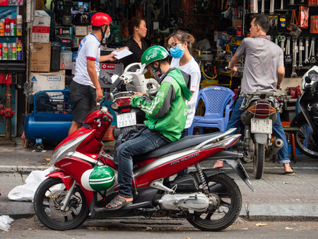 Ho Chi Minh City, Vietnam - April 3, 2019: Grab motorbike taxi driver checking the destination on his mobile phone before accepting a ride in Ho Chi Minh City, Vietnam. Grab has achieved more or less a monopoly on motorbike taxi services in the city.