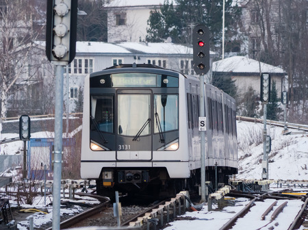Oslo, Norway - December 26, 2018: The city railway in Oslo, T-banen, arriving at Majorstuen Station with a frozen winter landscape in the background.