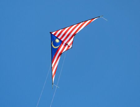 2-line stunt kite with the colours of the Malaysian flag flying on a blue sky background.