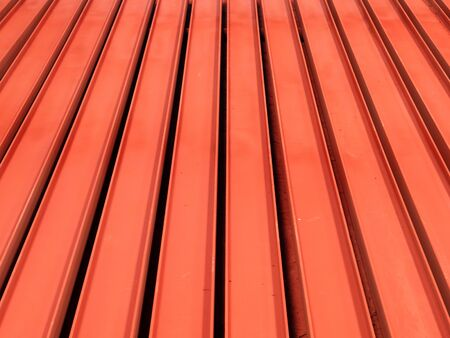 Red painted H-beams on the floor forming a linear pattern.