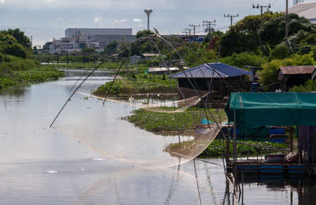 Canal at a heavily industrialised area at Bangsaothong District, Samut Prakan Province in Thailand. Even in the industrialised zones of Thailand, canals like these, or klongs, can be found behind the factories, where people mostly live their traditional lifestyle.