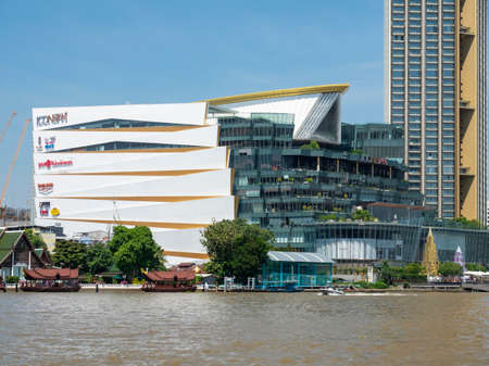 Bangkok, Thailand - October 24, 2020: Chao Praya River in Bangkok with Icon Siam shopping mall and residence towers, one of the newest luxury developments of the city.