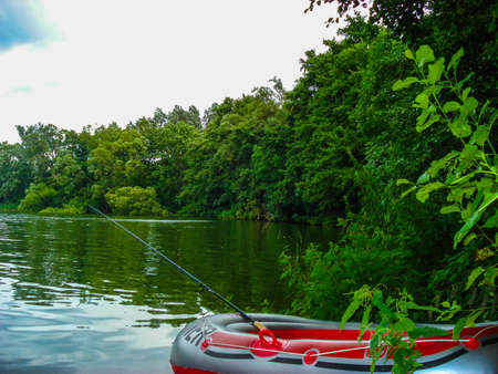 fishingpole: Fishing off an inflatable rubber dinghy on a tranquil lake. Nature background.