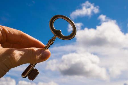 keys to heaven: The Key into hand, Sky Background Stock Photo