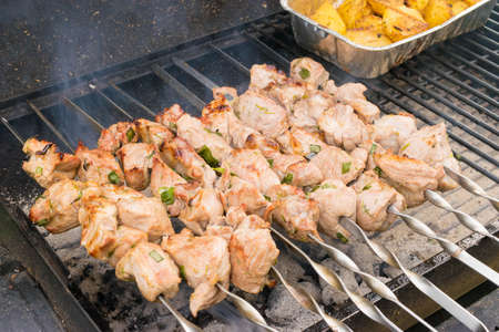 family reunion: Grilling marinated shashlik on grill. Friends meeting, family reunion, leisure and weekends. Stock Photo