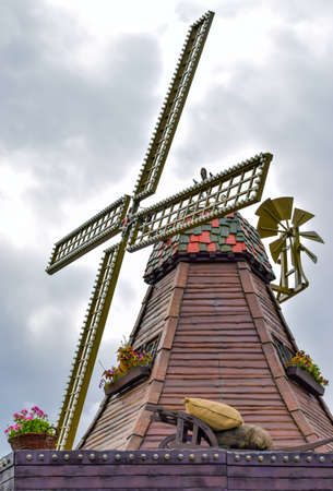 water turbine: Traditional old wooden windmill with decko against sky.