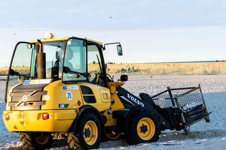 Rostock, Germany - August 19, 2016: Volvo L20F wheel loader at the beach of Rostock-Warnemuende. Coastal management.