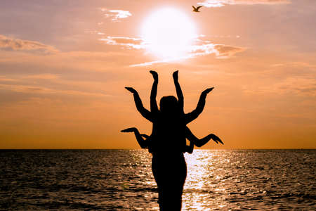 bharatanatyam: Indian dance silhouette on beautiful beach during sunset. Silhouette of human figure with many arms
