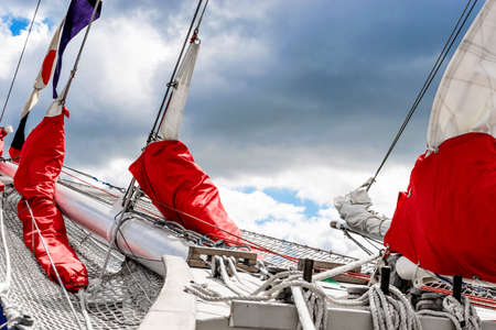 Bowsprit and gathered red sail of the sailing ship.