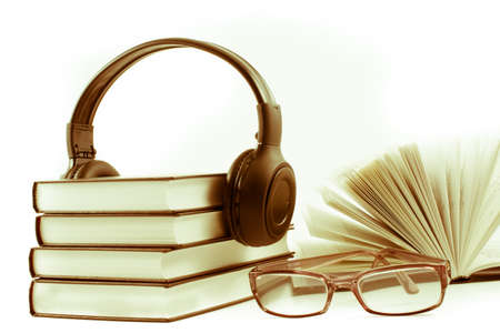 books with headphones and spectacles. Audio book concept Stock Photo