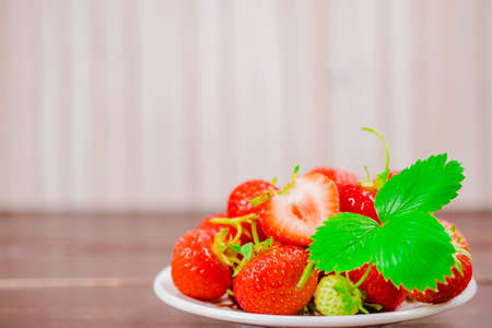strawberries in bowl on wooden table with low key and copy space Stock Photo