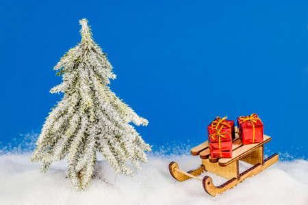 Weihnachtsbaum im Schnee unter Schneeflocken mit Schlitten und rotem Weihnachten Standard-Bild - 88884560