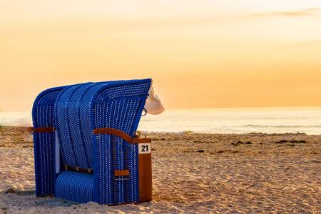 Blue beach basket, beach chair on the sea beach with sunset.