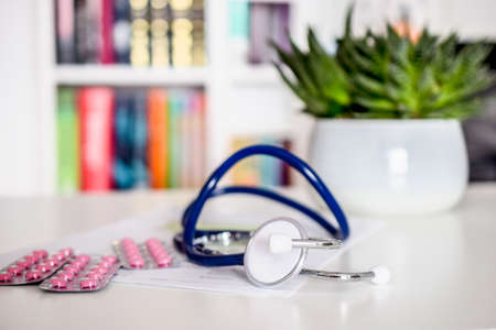 blue stethoscope and pink pills on white table in doctors office or in hospital with chair and bookshelf in the background