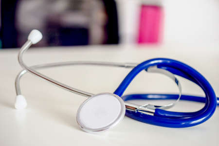 blue stethoscope on white table in doctors office or in hospital.
