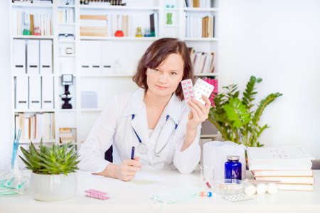 female doctor with stethoscope write prescription at workplace in office surrounded by various medications, pills, bandages and pills. women doctor hold in hand different pills.