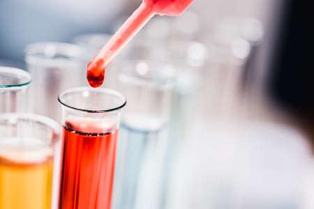 創薬、薬理学、バイオテクノロジーの概念。サンプルドロップが付いているテスト管およびピペット。実験室の科学の背景。