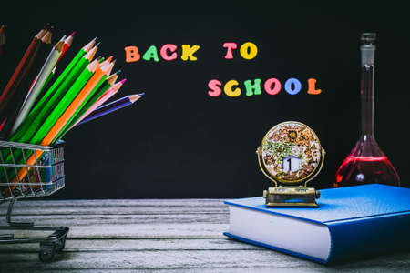 Back to School and Education concept. shopping cart with color pencils, book with red apple and calendar on chalkboard background. school border with copy space