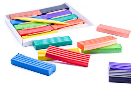 colorful plasticine in a box with a plastic knife on white background Stock fotó