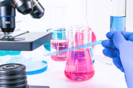 hand of scientist pouring into flask colorful liquid. examining samples in laboratory and close up of microscope . laboratory science, clinic and research concept.