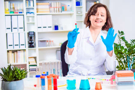 Scientist or doctor holds syringe in hands. handing stop hand to refuse vaccination. laboratory colored chemical reagents in laboratory - and test tubes. Personalized medicine and vaccine concept. Stock Photo