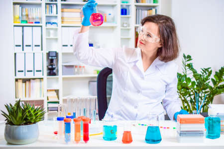 female scientist holding laboratory flask in hand. researcher researching in the laboratory. reagent flasks and test tubes with colored chemical reagents. Personalized medicine and vaccine concept. Stock Photo