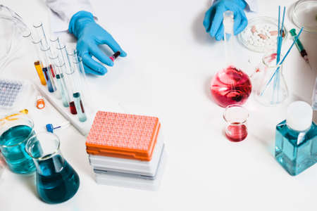 scientists holds blood sample in hand in laboratory. drug discovery, pharmacology and biotechnology concept. science and medical research background with pills and chemical tubes. top view. Stock Photo