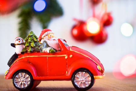 Santa Claus on Christmas toy car with gift boxes and pine tree on wooden table over blurred background with Christmas balls and fir tree. Xmas presents concept and Christmas border or greeting card