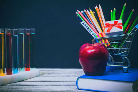 Back to School and Education shopping concept. classroom with apple, books, chemical test tubes and pencils on chalkboard background. school border with copy space Stock Photo