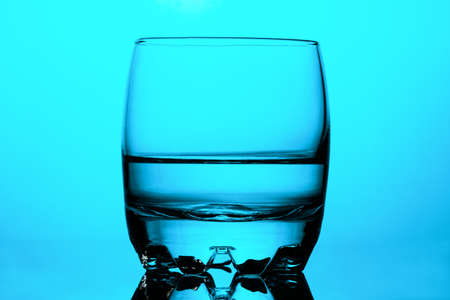 Clean drinking water in a round glass cup on blue background Stockfoto