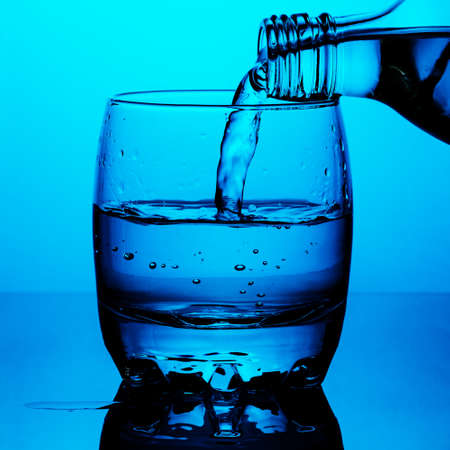 Clean drinking water is poured from a bottle a glass cup on blue background