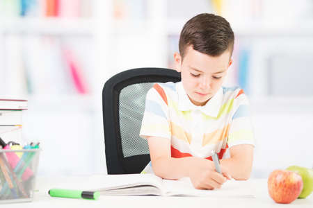 cute happy smiling boy on school homework. Back to school concept. Funny emotional teenager sitting at the desk with school homework. Bookshelf out of focus in the background 版權商用圖片