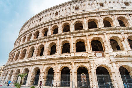 Roma, Italy - april 17, 2018: Colosseum and tourists in Rome. Italy capital landmarks. Colosseum or Amphitheatrum Flavium , a vast amphitheater in Rome. Travel, tourism and attractions