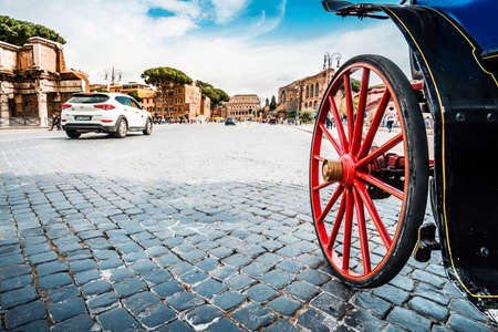 Roma, Italy - april 17, 2018: Colosseum and Forum Roman ruins. Wheel of horse-drawn carriage and tourists in Rome. Italy capital landmarks. Travel, tourism and attractions