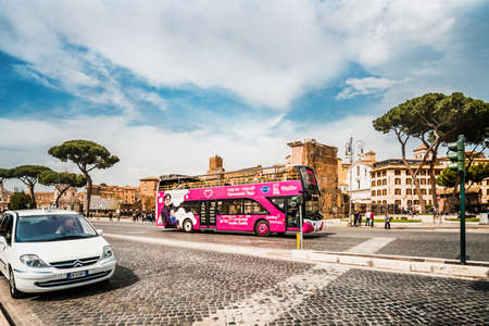Roma, Italy - april 17, 2018: Colosseum and Forum Roman ruins with tourist bus in Rome. Italy capital landmarks. Colosseum or Amphitheatrum Flavium. Travel, tourism and attractions