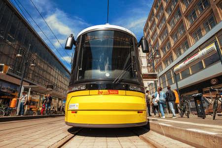 Berlin, Germany - July 12, 2018: traditional modern yellow tram in the city street in Berlin. Tram on tram station in Berlin. Editorial
