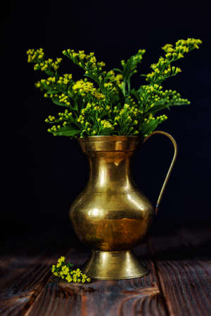 Yellow flower in old vase on wooden table. still life vintage picture in mood style