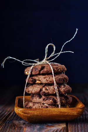 Stacked chocolate cookies on wooden table. Rustic food picture vertical