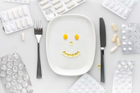 vitamins and supplements served on the plate with fork and knife. Breakfast with variety of colorful pills, tablets and capsules. supplements and medicine concept.
