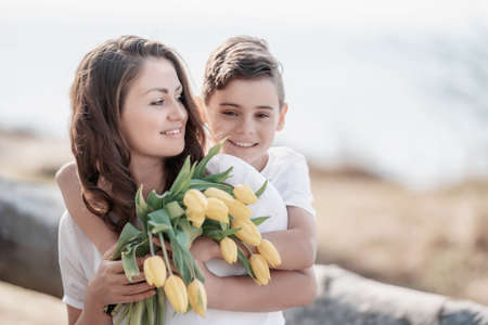 Happy mothers day! Child son congratulates mom and gives her flowers tulips. Mum and boy smiling and hugging. Mother and child in the nature. Family togetherness and family holiday Banco de Imagens