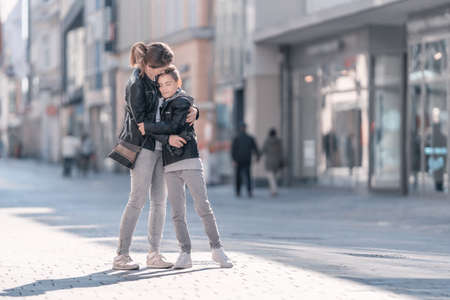 Portrait of a mother with her teenager son in the city. Young woman kisses and hugs her son. Mothers Day, Childrens day and Family Concept. Tenderness and love in the Family.