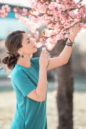 Young beautiful woman smells blooming sakura. Happy mothers day or happy woman day. Outdoor lifestyle. Freedom concept.