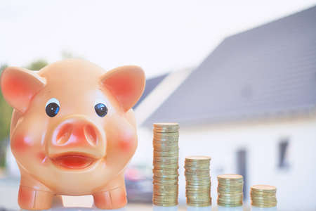 Piggy bank and home savings for homeowner and homebuilding . Real estate sale and loans market concept. Housing industry mortgage plan and residential tax saving. Piggy bank and coins stack isolated outside blurred home on background. Banco de Imagens