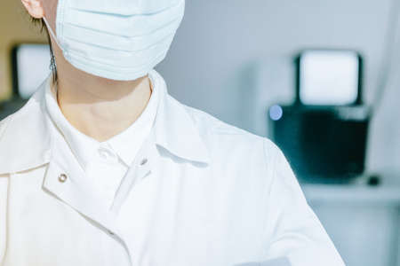 young woman in medical face protection mask and gloves indoors on laboratory background Standard-Bild