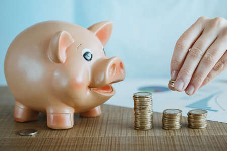 Female hand putting euro coin on top of a coin tower next to the piggy bank. Investments and savings conzept.