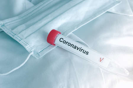 coronavirus test. Test tube lying on inspiratory protective respiratory mask. COVID-19 test or SARS-CoV-2 test.