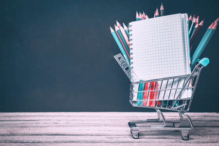 Back to School and Education concept. shopping cart with supplies, notebook and colorful pencils on chalkboard background. school border with copy space 版權商用圖片