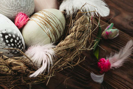 Close up of decorative Easter eggs in a basket on wooden background. Happy Easter card 版權商用圖片